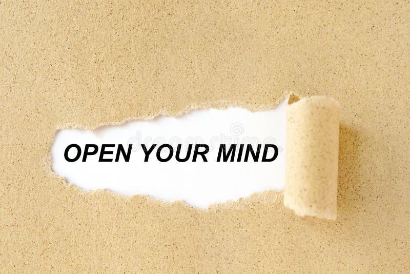 Ανοίξτε το μυαλό σας που εμφανίζεται πίσω από το καφετί έγγραφο χαρτονιού δακρυ'ων στοκ εικόνες