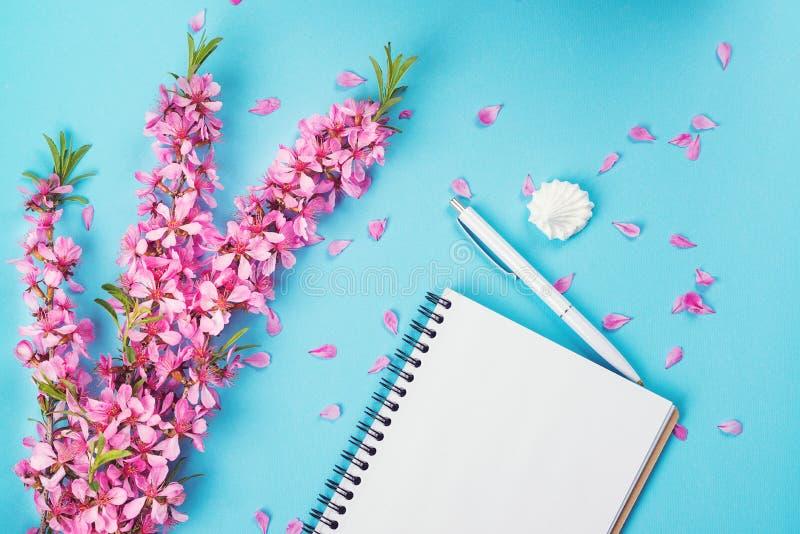 Ανοιγμένα λουλούδια σημειωματάριων και άνοιξη Χλεύη επάνω Ρόδινα λουλούδια άνοιξη στο μπλε υπόβαθρο εγγράφου Κενό σημειωματάριο γ στοκ φωτογραφία με δικαίωμα ελεύθερης χρήσης