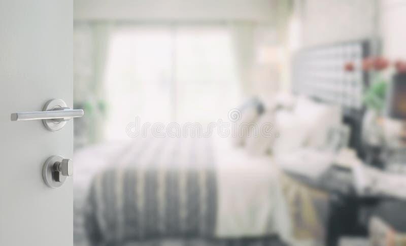 Ανοιγμένη άσπρη πόρτα στο θολωμένο υπόβαθρο της σύγχρονης κρεβατοκάμαρας στοκ φωτογραφίες