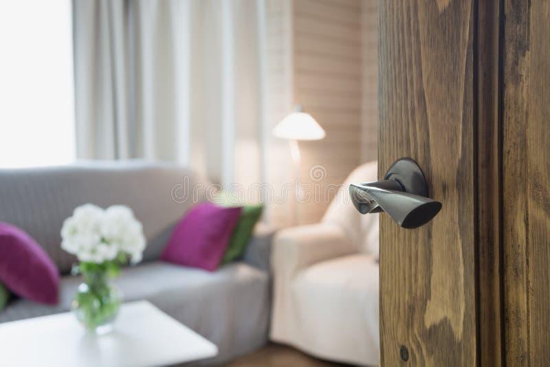 Ανοιγμένη ξύλινη πόρτα στο σύγχρονο εσωτερικό καθιστικών με την καρέκλα, μαλακό ντιβάνι και bouqet των λουλουδιών στον πίνακα στοκ εικόνες