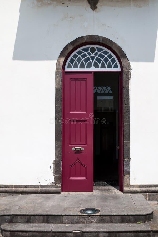 Ανοιγμένη burgundy πόρτα ενός σπιτιού στοκ εικόνα
