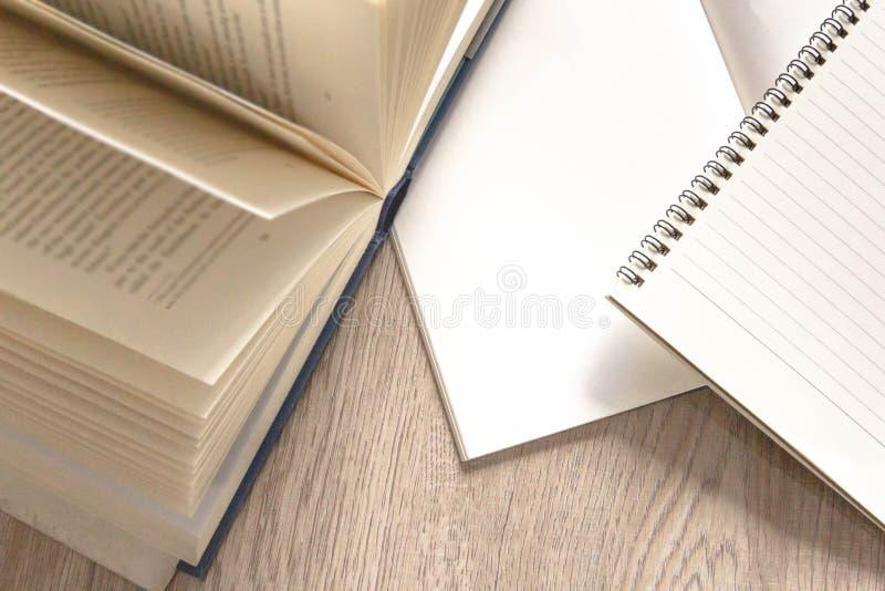 Ανοιγμένο βιβλίο και κενά σημειωματάρια στον ξύλινο πίνακα στοκ εικόνα
