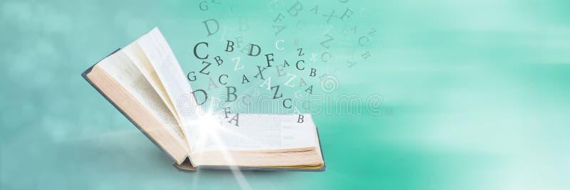 Ανοιγμένο βιβλίο με το φως και επιστολές στο πράσινο υπόβαθρο στοκ εικόνες