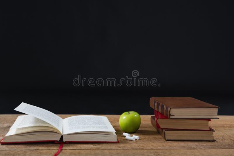 Ανοιγμένο βιβλίο με το πράσινους μήλο και το σωρό βιβλίων στοκ φωτογραφίες