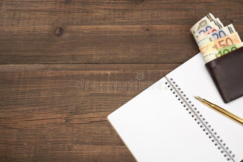 Ανοιγμένο σπειροειδές σημειωματάριο, πορτοφόλι με τα ευρο- μετρητά, μάνδρα στο ξύλο στοκ εικόνα