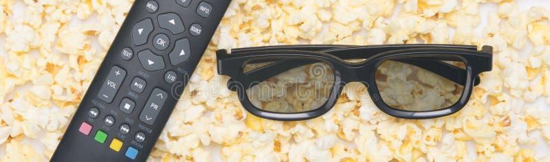 Ανοιγμένο τηγανισμένο popcorn, κινηματογράφηση σε πρώτο πλάνο, ως υπόβαθρο με τα τρισδιάστατα γυαλιά και έναν τηλεχειρισμό TV στοκ εικόνα με δικαίωμα ελεύθερης χρήσης