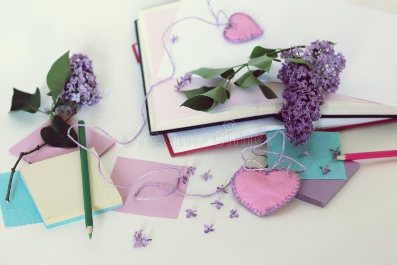 Ανοικτά βιβλία, καρδιές σελιδοδεικτών, έγγραφο, μολύβια, κλάδοι των ιωδών λουλουδιών στον πίνακα στοκ εικόνες