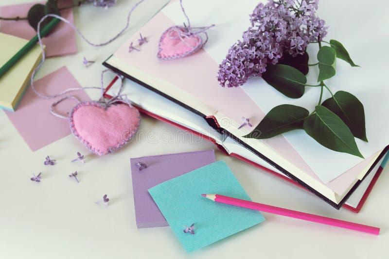 Ανοικτά βιβλία, καρδιές σελιδοδεικτών, έγγραφο, μολύβια, κλάδοι των ιωδών λουλουδιών στον πίνακα στοκ φωτογραφίες