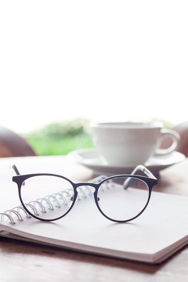 Ανοικτά κενά άσπρα σημειωματάριο και eyeglasses με το φλιτζάνι του καφέ στοκ φωτογραφίες