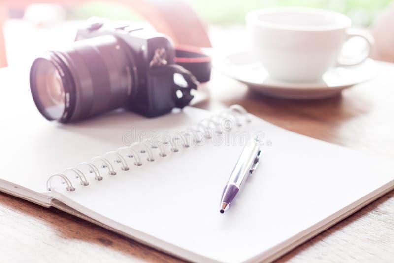 Ανοικτές κενές άσπρες σημειωματάριο και μάνδρα με το φλιτζάνι του καφέ στοκ εικόνες