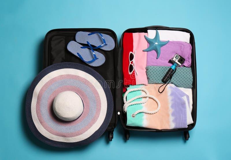 Ανοικτή βαλίτσα με τις ταξιδιωτικές περιουσίες στο υπόβαθρο χρώματος στοκ εικόνες