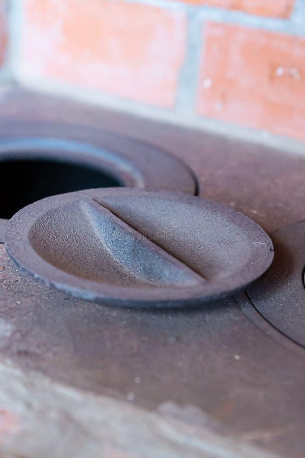 Ανοικτή παραδοσιακή σόμπα κινηματογραφήσεων σε πρώτο πλάνο τούβλου φούρνων μετάλλων καυστήρων που μαγειρεύει την κάθετη φωτογραφί στοκ φωτογραφία