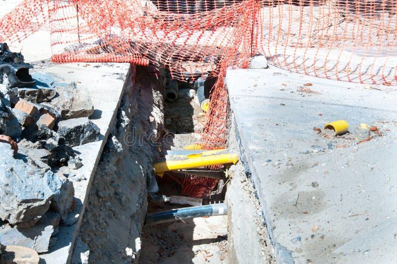 Ανοικτή τάφρος στην περιοχή ανασκαφής οδών με τους ορατούς σωλήνες για το αέριο νερού και το σύστημα θέρμανσης στοκ φωτογραφία με δικαίωμα ελεύθερης χρήσης