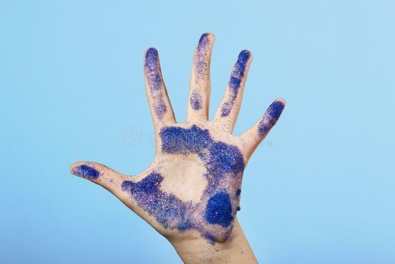 Ανοικτός φοίνικας που ψεκάζεται με τις μπλε μεταλλικές πούλιες Χέρι που αυξάνεται, μόρια της θρυμματιμένος σκόνης στοκ φωτογραφία