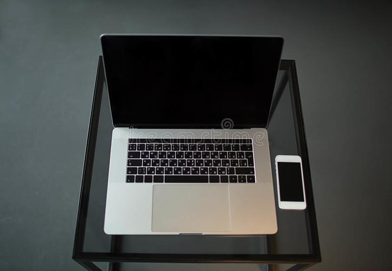 Ανοικτός φορητός προσωπικός υπολογιστής και σύγχρονο κινητό τηλέφωνο με τις κενές οθόνες που βρίσκονται σε έναν πίνακα γυαλιού στοκ φωτογραφία με δικαίωμα ελεύθερης χρήσης