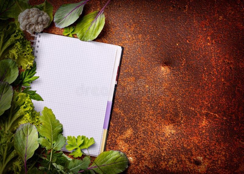 Ανοικτό βιβλίο επιλογών με τα φρέσκα πράσινα στοκ φωτογραφίες