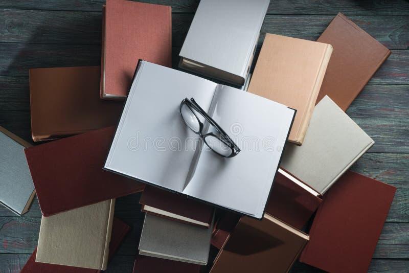 Ανοικτό βιβλίο με σκληρό εξώφυλλο βιβλίων στα βιβλία σωρών στο ξύλινο υπόβαθρο στοκ εικόνα με δικαίωμα ελεύθερης χρήσης