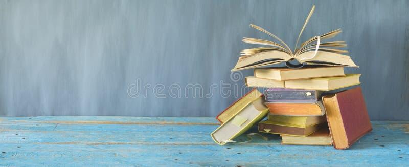 Ανοικτό βιβλίο σε έναν σωρό των παλαιών βιβλίων, πανόραμα στοκ φωτογραφίες