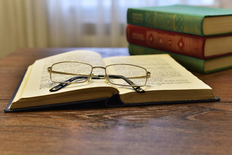 Ανοικτό βιβλίο με τα γυαλιά και το σωρό των βιβλίων στοκ εικόνα με δικαίωμα ελεύθερης χρήσης