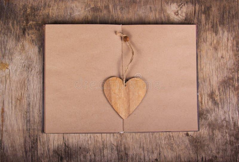 Ανοικτό βιβλίο με τις κενές σελίδες και ένας σελιδοδείκτης υπό μορφή καρδιάς Σημειωματάριο που γίνεται από το ανακυκλωμένους έγγρ στοκ εικόνα