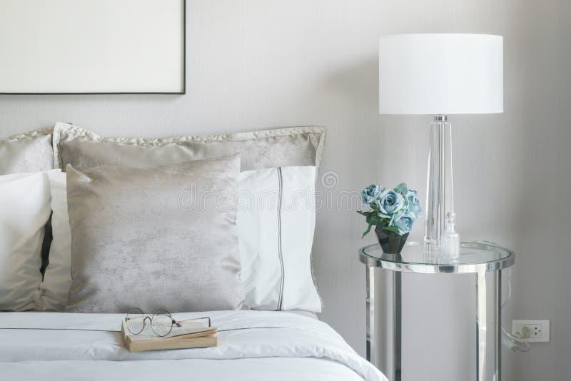 Ανοικτό γκρι και άσπρα μαξιλάρια στο κρεβάτι με το βάζο λουλουδιών στον πίνακα πλευρών στοκ φωτογραφία