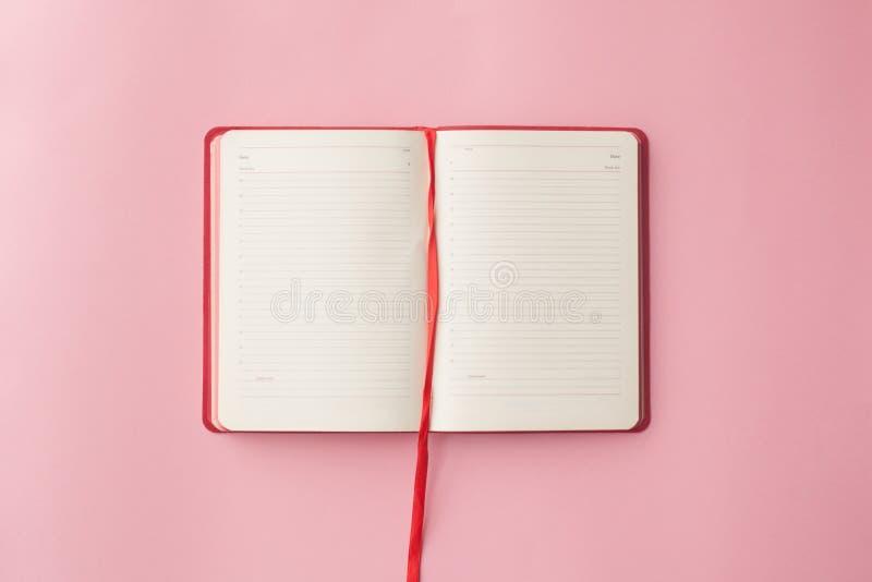 Ανοικτό ημερολόγιο με μια μάνδρα σε ένα ρόδινο υπόβαθρο Τοπ όψη Εκλεκτική εστίαση χρυσή ιδιοκτησία βασικών πλήκτρων επιχειρησιακή στοκ εικόνες