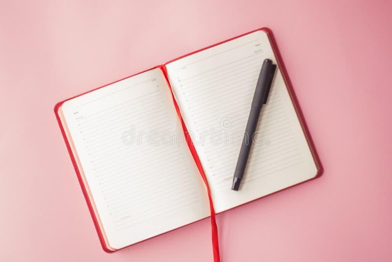 Ανοικτό ημερολόγιο με μια μάνδρα σε ένα ρόδινο υπόβαθρο Τοπ όψη Εκλεκτική εστίαση χρυσή ιδιοκτησία βασικών πλήκτρων επιχειρησιακή στοκ φωτογραφία με δικαίωμα ελεύθερης χρήσης