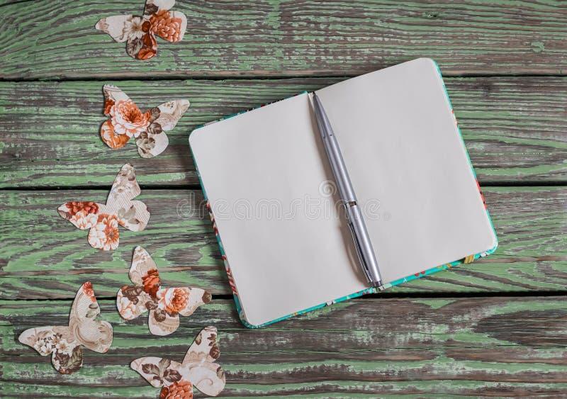 Ανοικτό καθαρό σημειωματάριο και σπιτική πεταλούδα εγγράφου σε ένα ξύλινο εκλεκτής ποιότητας υπόβαθρο Τοπ άποψη, ελεύθερου χώρου  στοκ εικόνα με δικαίωμα ελεύθερης χρήσης