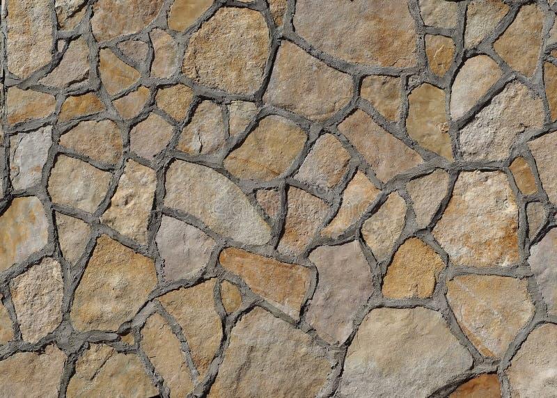 Ανοικτό καφέ τοίχος πετρών φιαγμένος από ανώμαλες μεγάλες επίπεδες φυσικές πέτρες με πολύ σκυρόδεμα στα σύνορα στοκ εικόνες με δικαίωμα ελεύθερης χρήσης