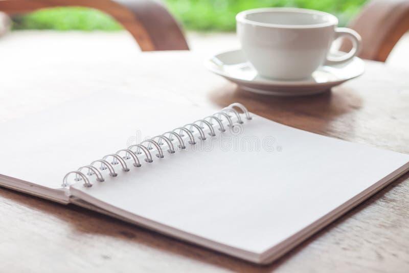 Ανοικτό κενό άσπρο σημειωματάριο με το φλιτζάνι του καφέ στοκ εικόνες