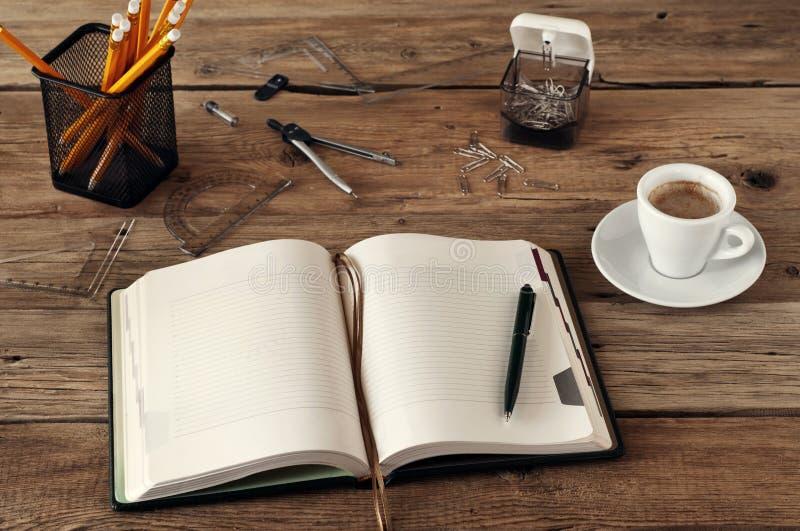 Ανοικτό κενό σημειωματάριο σε ένα ξύλινο γραφείο με ένα φλυτζάνι του μαύρου καφέ, στοκ φωτογραφίες