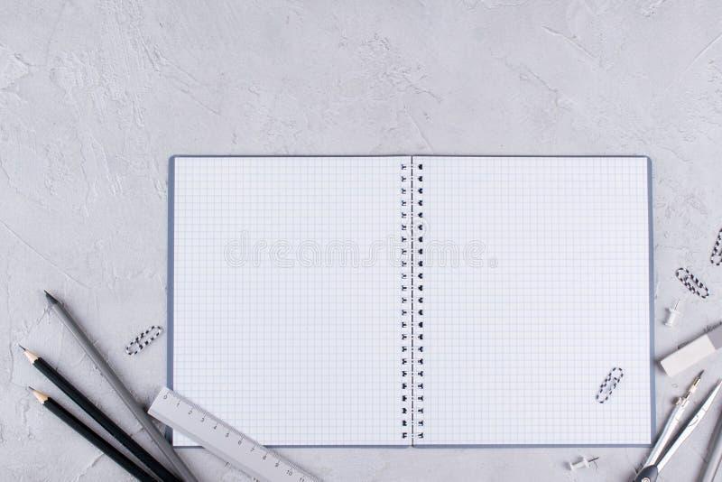 Ανοικτό κενό σπειροειδές σημειωματάριο, γκρίζες σχολικές προμήθειες στο συγκεκριμένο υπόβαθρο Επίπεδος βάλτε στοκ φωτογραφία