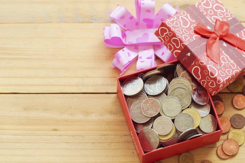 Ανοικτό κιβώτιο δώρων με τα νομίσματα στο ξύλινο υπόβαθρο στοκ εικόνες