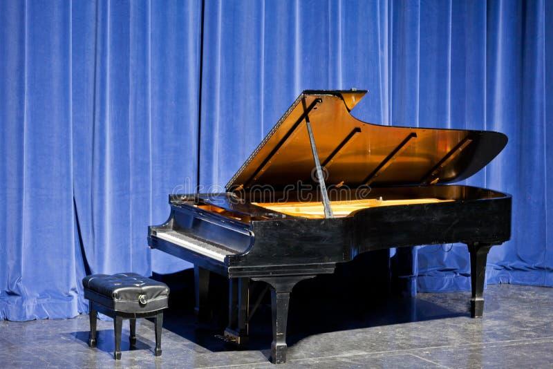 Ανοικτό μεγάλο πιάνο στη σκηνή με το μπλε βελούδο cutain στοκ εικόνες