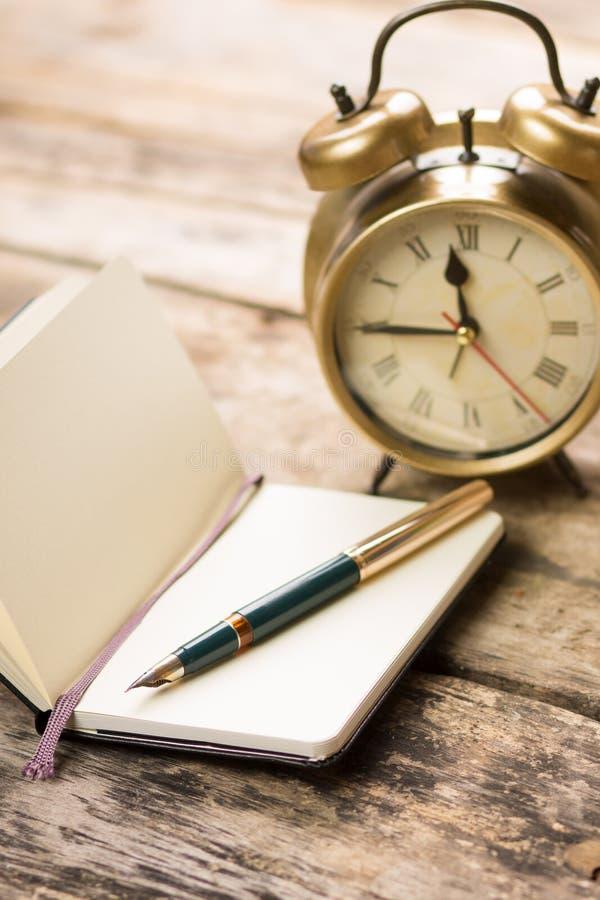 Ανοικτό μικρό σημειωματάριο με τη μάνδρα πηγών και το ντεμοντέ ξυπνητήρι πίσω στοκ φωτογραφία με δικαίωμα ελεύθερης χρήσης