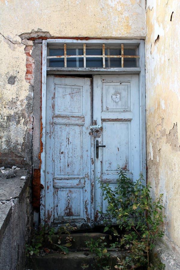 Ανοικτό μπλε παλαιές ξύλινες πόρτες που κλειδώνονται με το μικρό λουκέτο στο εγκαταλειμμένο σπίτι στοκ φωτογραφίες