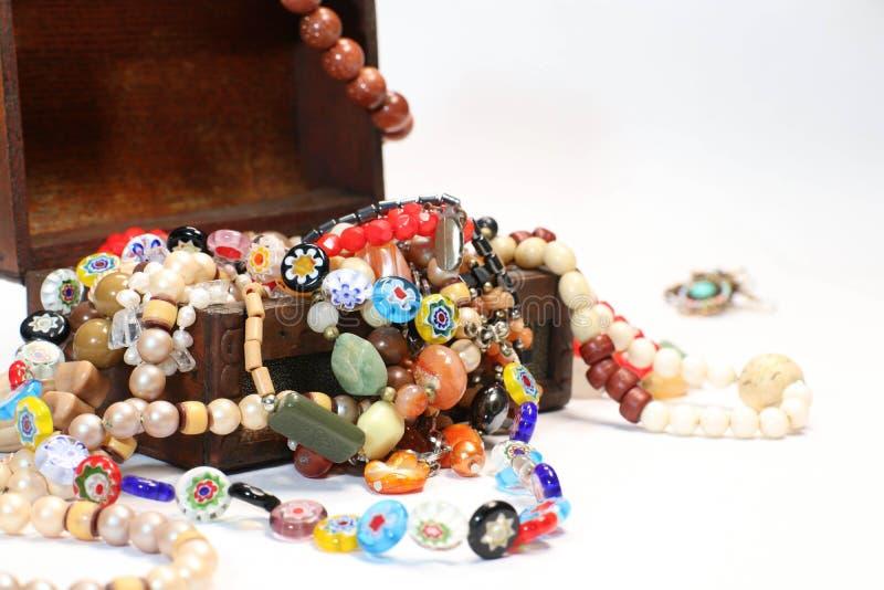 Ανοικτό ξύλινο κιβώτιο κοσμήματος με τις χρωματισμένες χάντρες και τα θολωμένα σκουλαρίκια στοκ φωτογραφίες