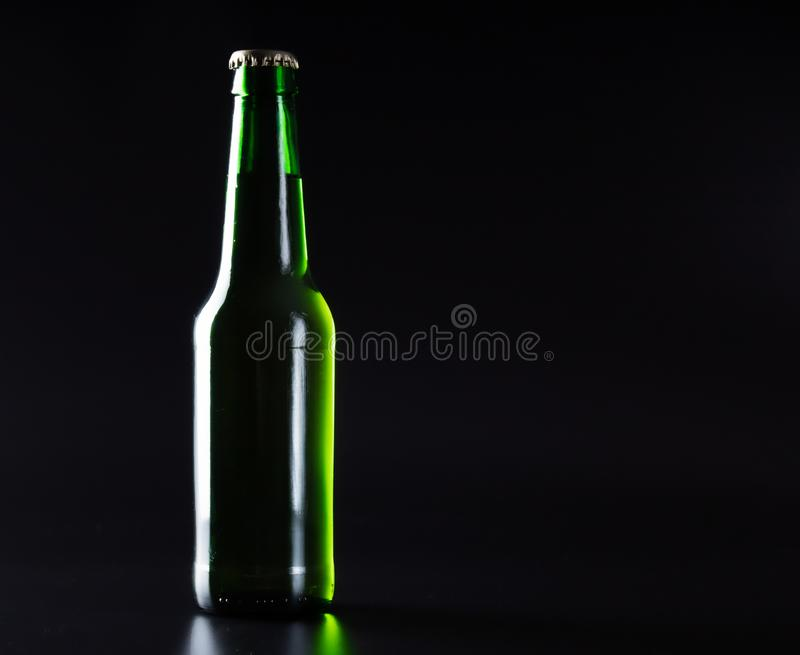 ανοικτό πράσινο μπουκάλι μπύρας στο Μαύρο στοκ εικόνα