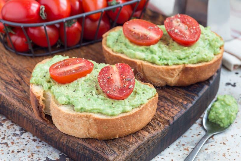 Ανοικτό σάντουιτς με τις πολτοποιηίδες ντομάτες αβοκάντο και κερασιών στο ψημένο ψωμί, που ψεκάζεται με το μαύρο πιπέρι, οριζόντι στοκ εικόνες με δικαίωμα ελεύθερης χρήσης