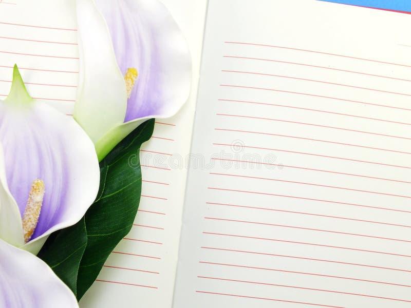 Ανοικτό σημειωματάριο και όμορφη calla τεχνητή ιώδης ανθοδέσμη λουλουδιών στοκ εικόνα με δικαίωμα ελεύθερης χρήσης