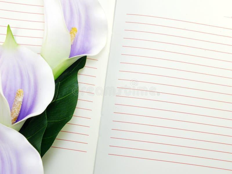 Ανοικτό σημειωματάριο και όμορφη calla τεχνητή ιώδης ανθοδέσμη λουλουδιών στοκ εικόνα