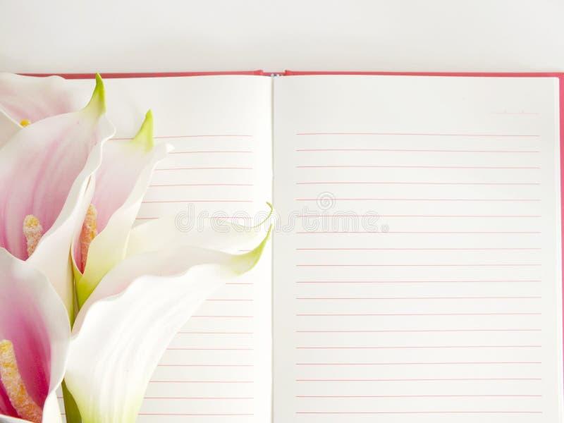 Ανοικτό σημειωματάριο και όμορφη calla τεχνητή ρόδινη ανθοδέσμη λουλουδιών στοκ εικόνα