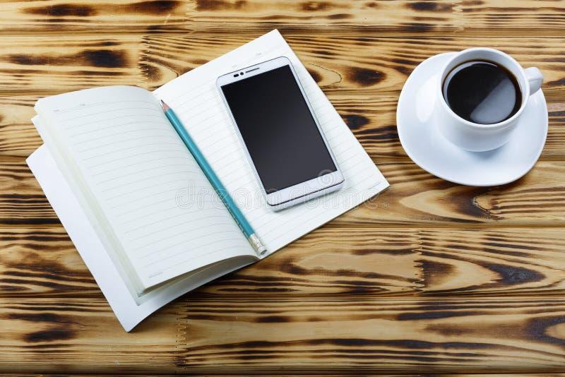 Ανοικτό σημειωματάριο, κενές σελίδες, μολύβι, άσπρο smartphone, φλυτζάνι του μαύρου καφέ στον πίνακα γραφείων ή στον πίνακα σε έν στοκ φωτογραφίες