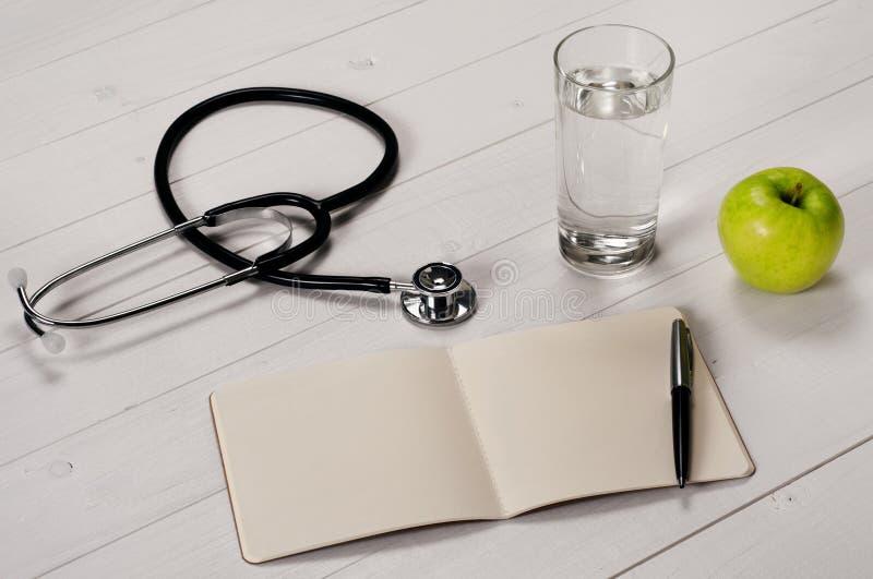 Ανοικτό σημειωματάριο με τη μάνδρα, το στηθοσκόπιο, το μήλο και ένα νερό γυαλιού στοκ φωτογραφία με δικαίωμα ελεύθερης χρήσης