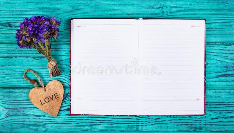 Ανοικτό σημειωματάριο με τις κενές σελίδες και ξύλινη καρδιά σε ένα μπλε υπόβαθρο διάστημα αντιγράφων στοκ εικόνες