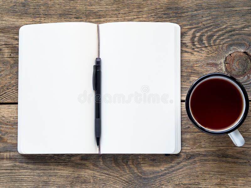 Ανοικτό σημειωματάριο σε ένα ελατήριο με τη Λευκή Βίβλο για τις σημειώσεις και το σχέδιο κοντά σε ένα μολύβι και ένα φλυτζάνι του στοκ φωτογραφία με δικαίωμα ελεύθερης χρήσης