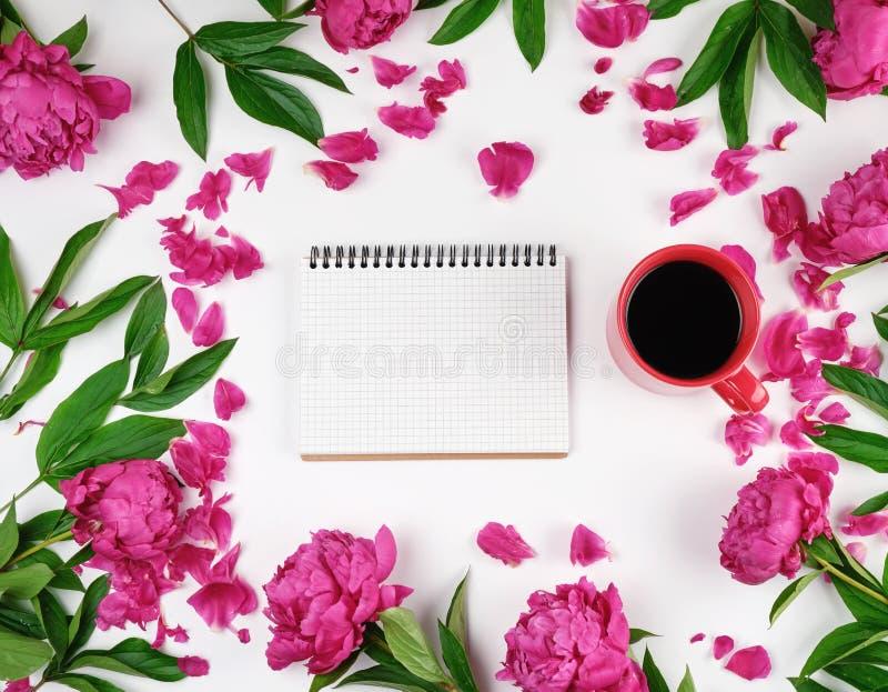 ανοικτό σημειωματάριο σε ένα κλουβί και ένα κόκκινο φλιτζάνι του καφέ σε ένα άσπρο υπόβαθρο στοκ εικόνα με δικαίωμα ελεύθερης χρήσης