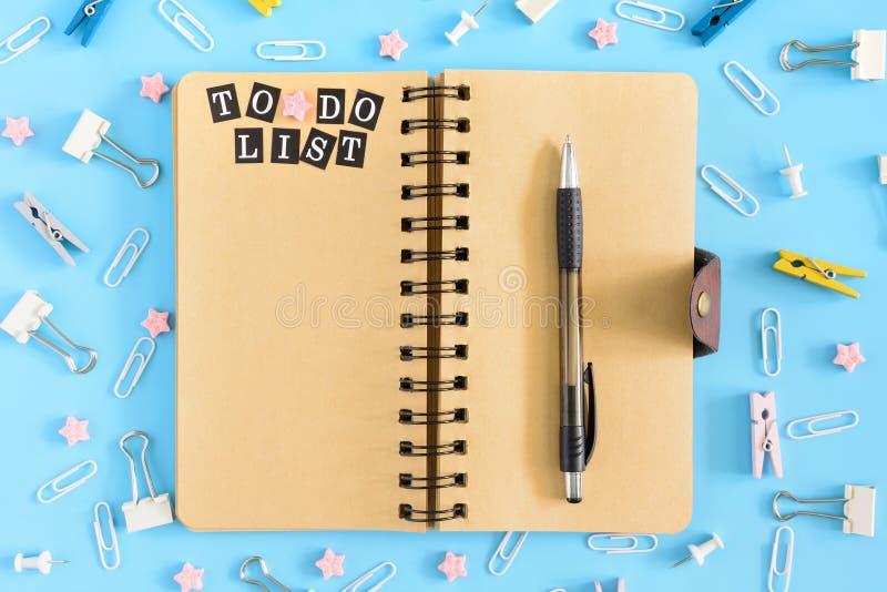 Ανοικτό σημειωματάριο στα ελατήρια με μια επιγραφή για να κάνει τα χαρτικά καταλόγων razrosannye σε ένα μπλε υπόβαθρο Γραφείου κο στοκ φωτογραφία