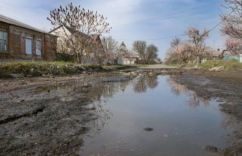 Ανοιξιάτικος αγροτικός δρόμος με ανθισμένους κήπους και έναν κακό σπασμένο δρόμο στοκ φωτογραφία