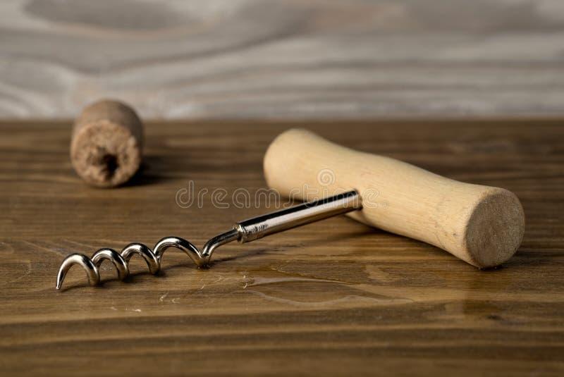 Ανοιχτήρι με το φελλό στο παλαιό ξύλινο υπόβαθρο στοκ φωτογραφία